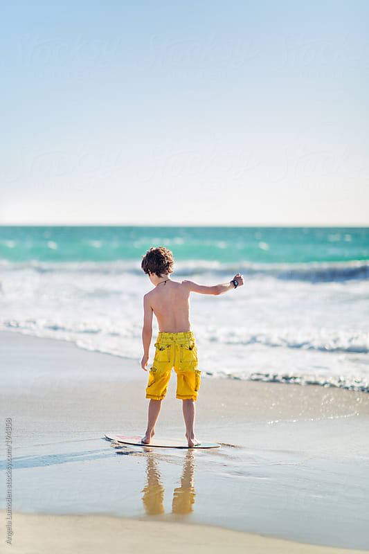 Boy riding a skim board at the beach by Angela Lumsden for Stocksy United