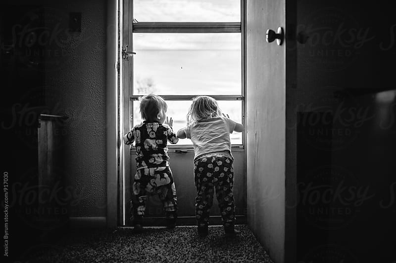 Two toddlers looking out of screen door by Jessica Byrum for Stocksy United