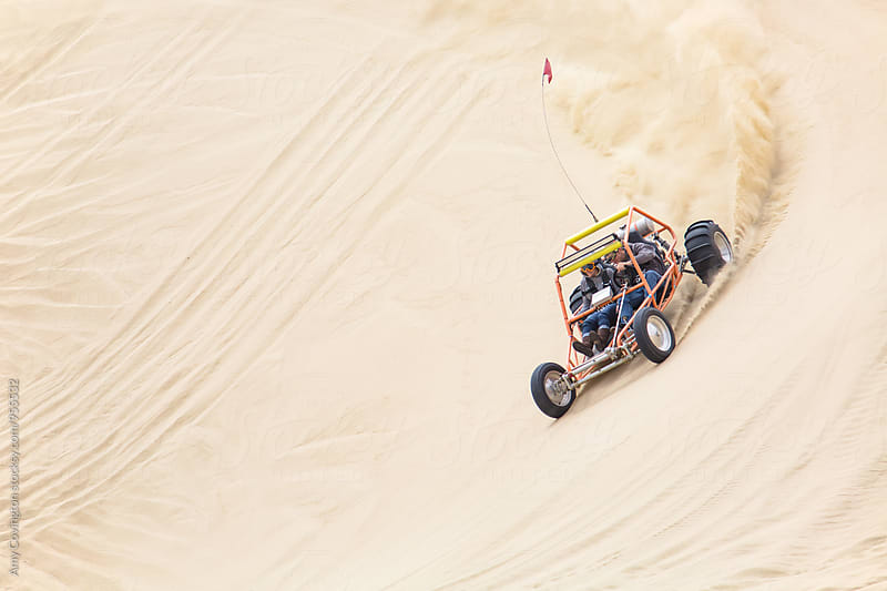 Sand rail racing through the sand dunes by Amy Covington for Stocksy United