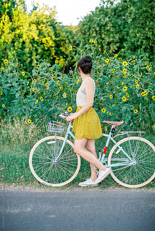 Woman walking with bike by Daniel Kim Photography for Stocksy United