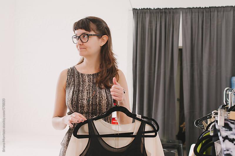 Woman Clothing Designer Holding Fashionable Wardrobe by Briana Morrison for Stocksy United