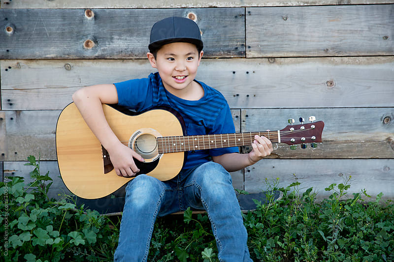 Asian boy playing guitar and smiling by Curtis Kim for Stocksy United