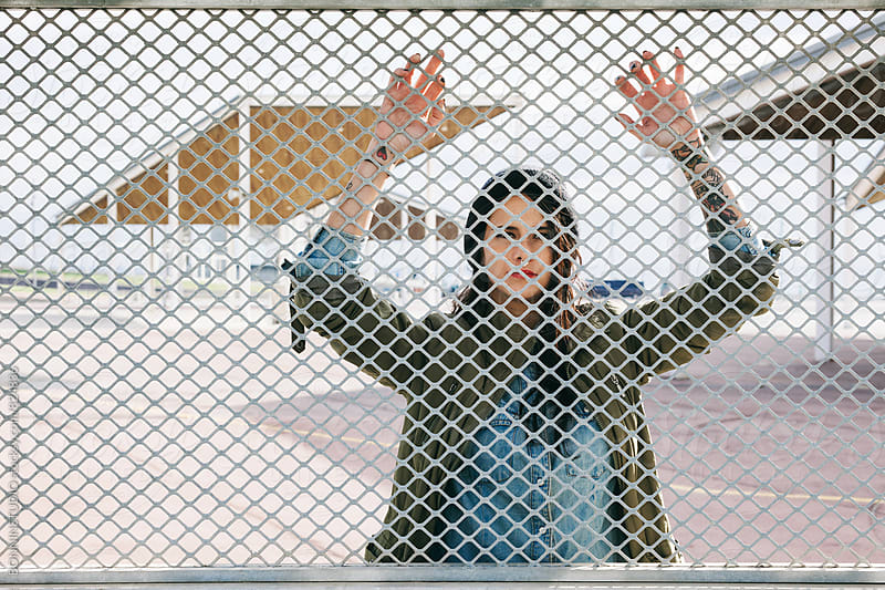 Portrait of an alternative brunette female standing through a fence. by BONNINSTUDIO for Stocksy United