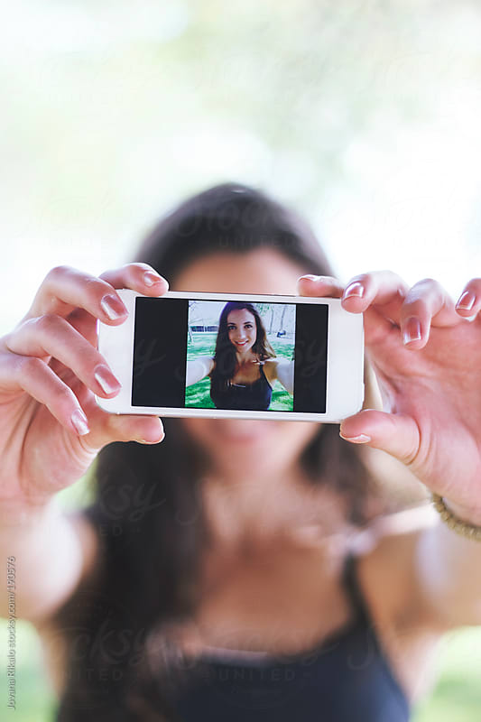 Young woman taking selfie with smart phone by Jovana Rikalo for Stocksy United