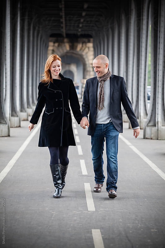 Couple in Paris walking hand in hand by Shelly Perry for Stocksy United