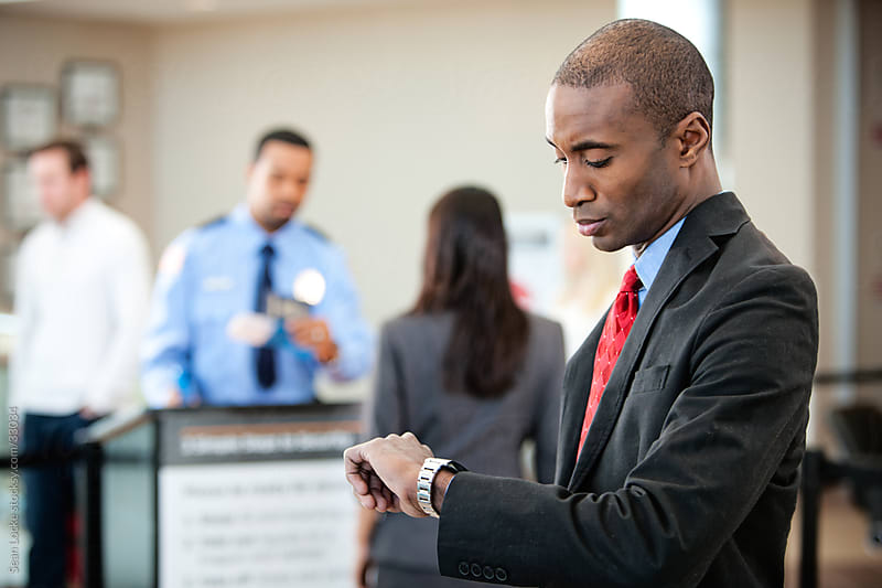 Airport: Impatient Traveler Checks Watch Near Security by Sean Locke for Stocksy United