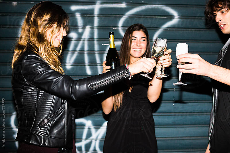 Group of friends toasting with champagne together by michela ravasio for Stocksy United