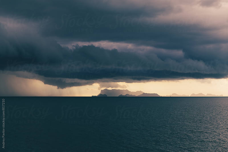 Beautiful photo of storm clouds above the dark blue ocean by Andrey Pavlov for Stocksy United