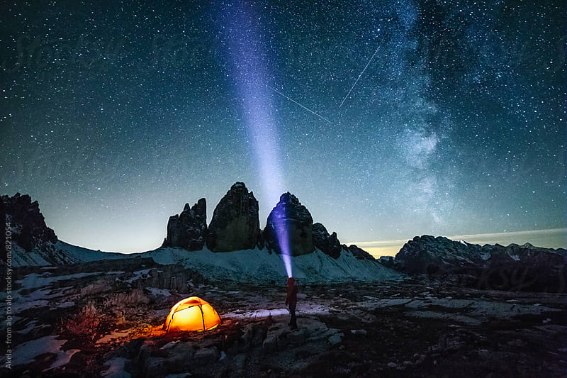 male adventurer with strong headlamp beside illuminated red orange under the milky way at the three pinnacles by Leander Nardin for Stocksy United
