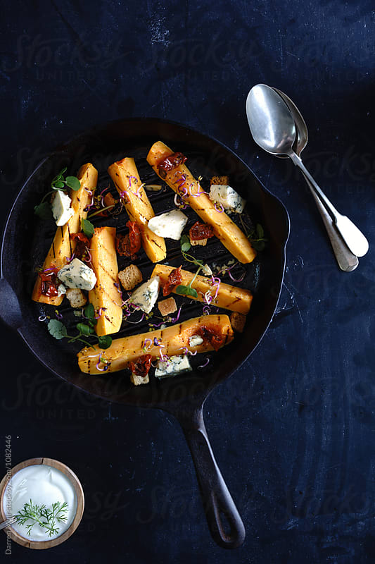 Roasted butternut squash wedges with blue cheese. by Darren Muir for Stocksy United