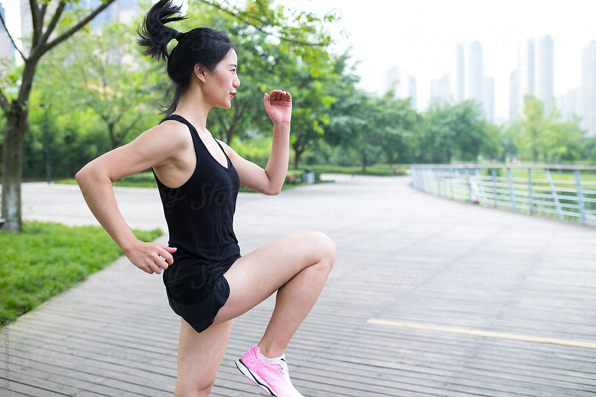 Young Asian Woman Doing Exercise In The Park by Bo Bo - Copyspace
