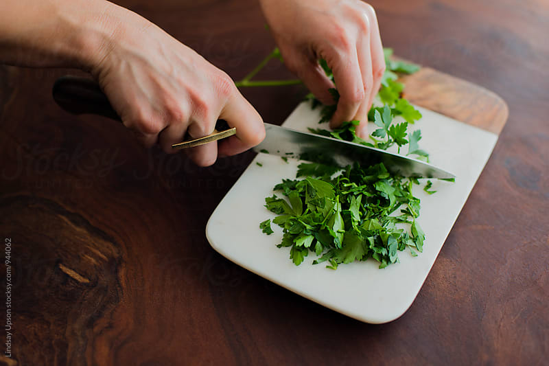 Hands cutting parsley by Lindsay Upson for Stocksy United
