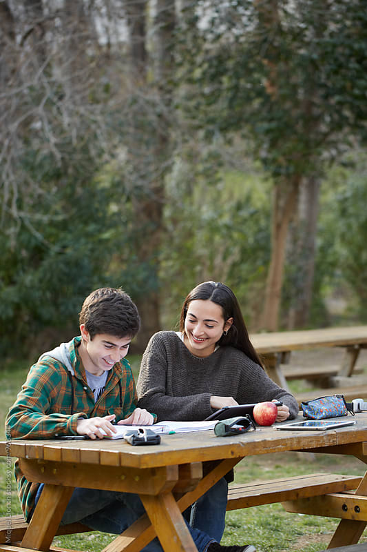 Young couple of students together at the campus of the university by Miquel Llonch for Stocksy United