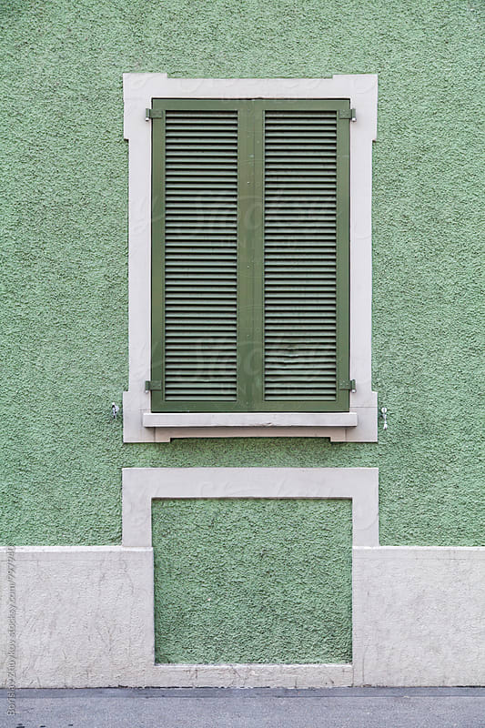 Green wall and wooden window shutter in Zurich, Switzerland  by Borislav Zhuykov for Stocksy United