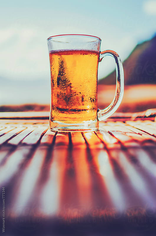 Ice cold jug of beer on a hot summer day on table by Wizemark for Stocksy United