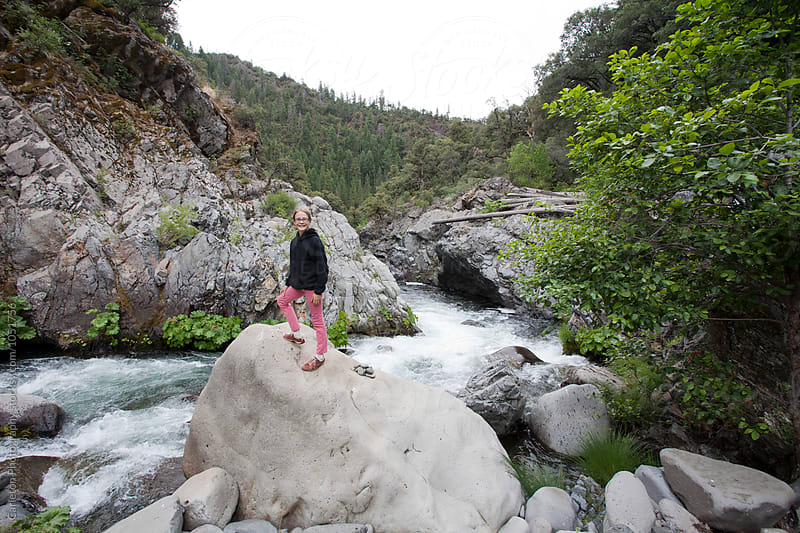 Girl stands atop a boulder next to a rushing creek by Carleton Photography for Stocksy United