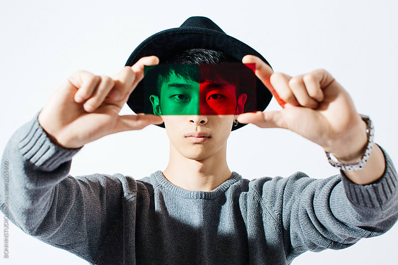 Portrait of an asian man looking through green and red glass. by BONNINSTUDIO for Stocksy United