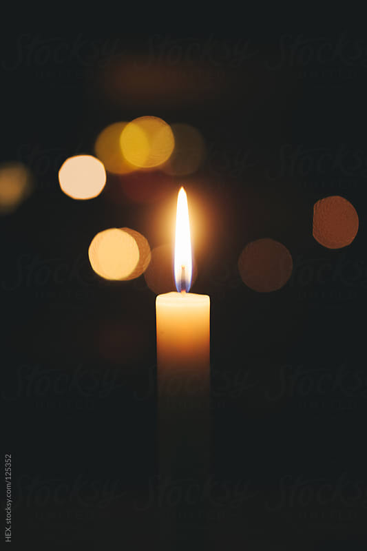 Single candle flame, black background by HEX. for Stocksy United