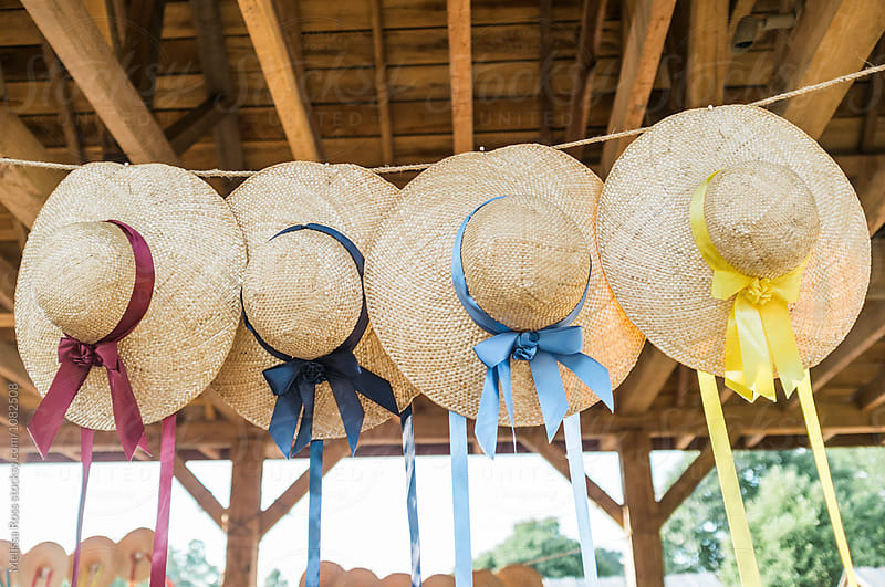 A display of straw hats. by Melissa Ross for Stocksy United