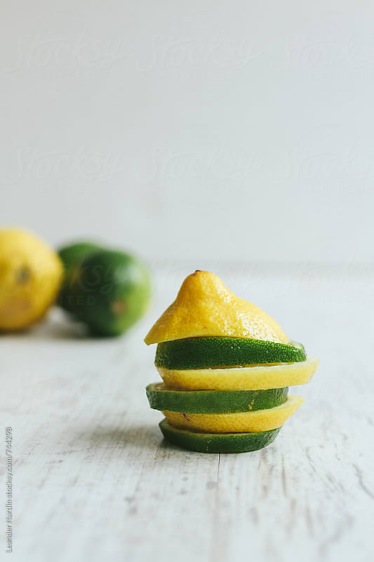 stacked slices from lemons and limes on white background by Leander Nardin for Stocksy United