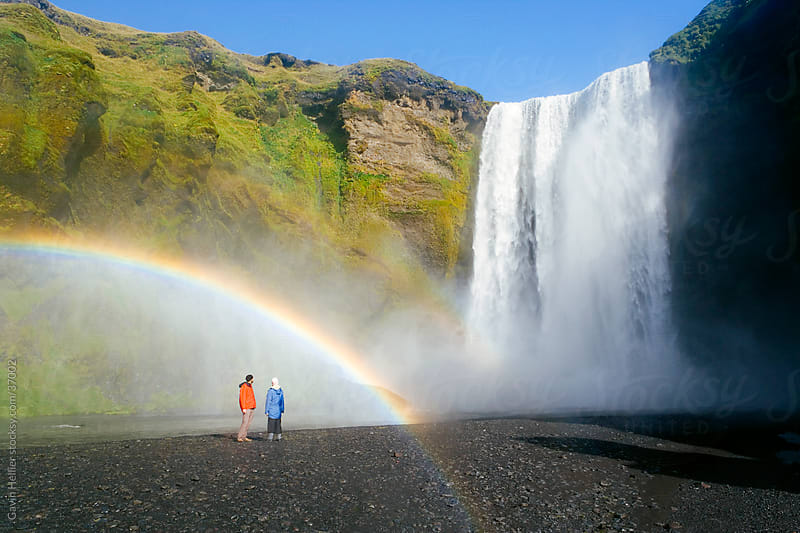 Iceland, Skogar, Skogafoss Falls, southern Iceland. Visitors standing in front of the Falls. Skogafoss is one of 20 waterfalls found along the Skogar River. The waterfall is 60 meters high. by Gavin Hellier for Stocksy United