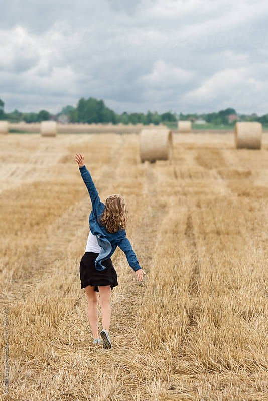 Woman having fun walking on a field with hay bales by RG&B Images for Stocksy United