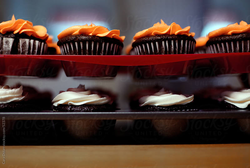 Two trays of cupcakes, orange and white frosting by Cara Dolan for Stocksy United
