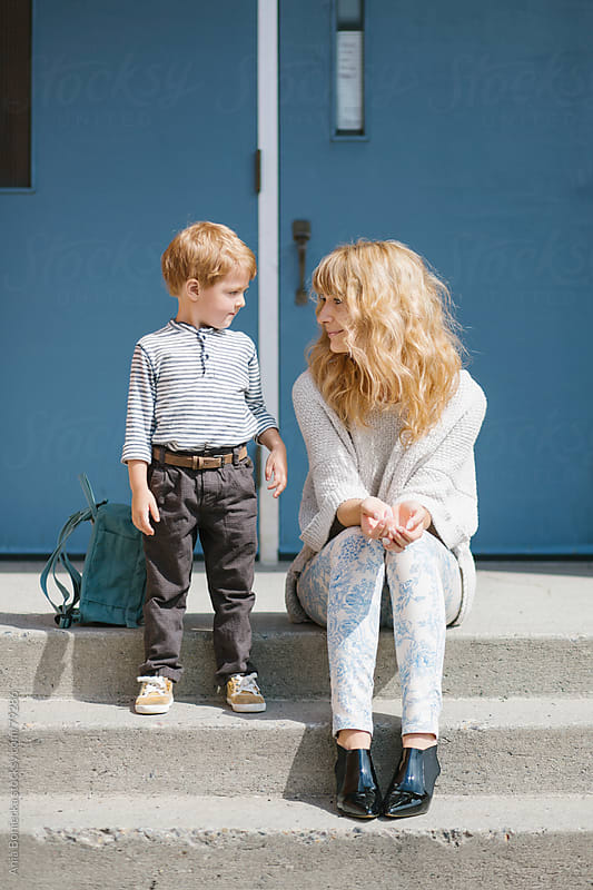 Mother and son sitting on the front steps of a school by Ania Boniecka for Stocksy United