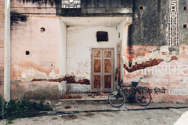Old bicycle leaning on a rustic wall next to a doorway by Maresa Smith for Stocksy United