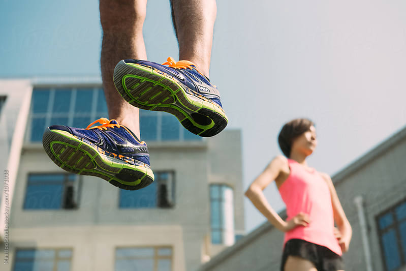Female and male runner standing on a glass floor by Maa Hoo for Stocksy United