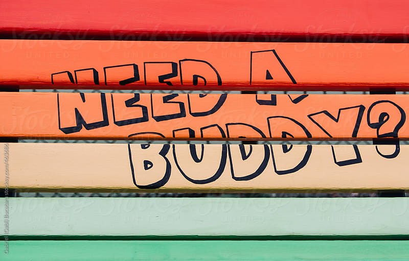 Rainbow colored bench with Need a Buddy written on it by Gabriel (Gabi) Bucataru for Stocksy United