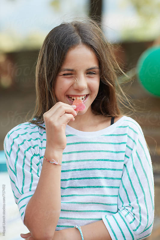 Young girl biting a gummy candy by Miquel Llonch for Stocksy United
