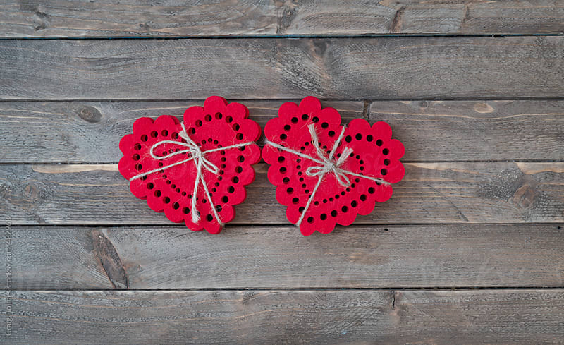 Heart shapes tied together on a wooden background. by Craig Holmes for Stocksy United
