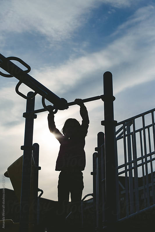 Silhouette of girl at playground by Amanda Worrall for Stocksy United