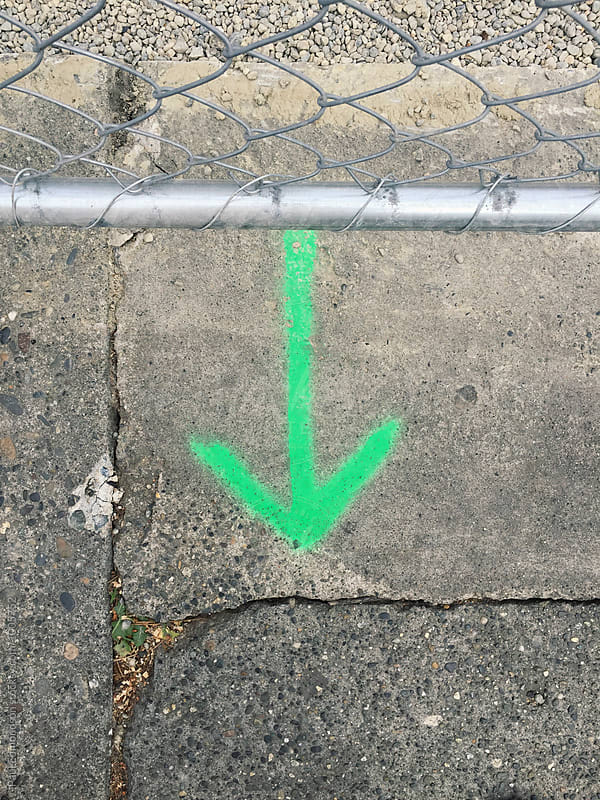 Green arrow painted on sidewalk, chain-link fence in foreground by Paul Edmondson for Stocksy United