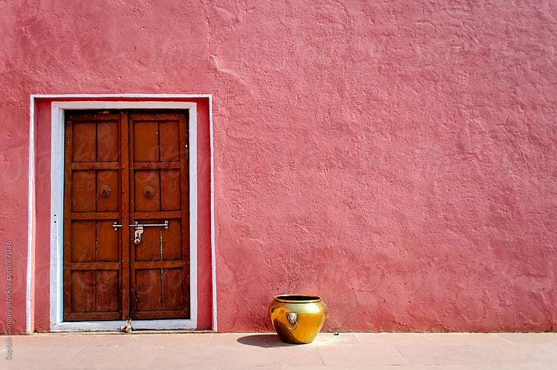 Pink wall the door and a golden colored pot by Saptak Ganguly for Stocksy United