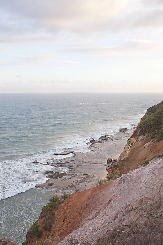 view from top of cliffs looking down at the ocean at sunset by Natalie JEFFCOTT for Stocksy United