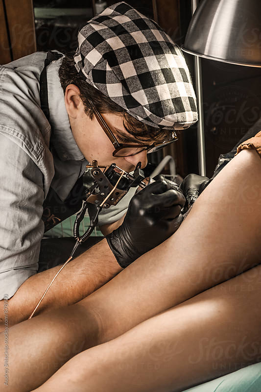 Tattoo session in vintage tatto studio. by Marko Milanovic for Stocksy United