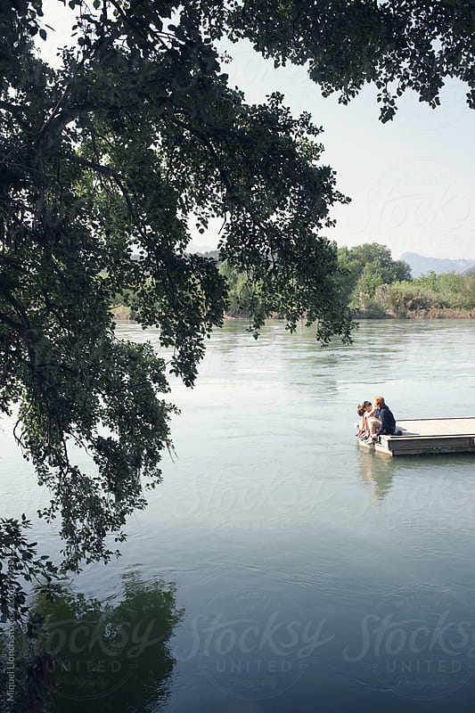 Teenager friends sitting on a dock at a river watching the water by Miquel Llonch for Stocksy United