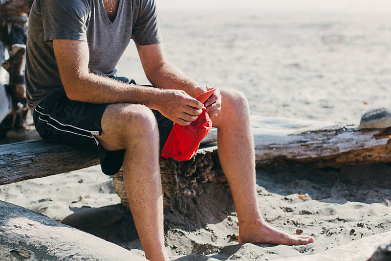 A Young Man Sitting On Driftwood Holds A Red Cap In His Hands On The Beach by Luke Mattson for Stocksy United