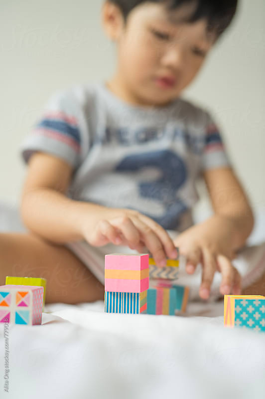 Boy playing with colourful wooden blocks by Alita Ong for Stocksy United