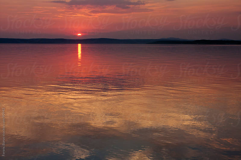 Colorful sky of sunset reflecting on a lake by Ferenc Boros for Stocksy United