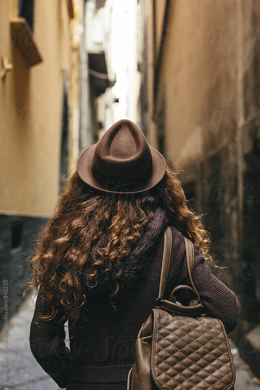 Young woman with hat walking down a narrow street in Naples, Italy by Aleksandar Novoselski for Stocksy United