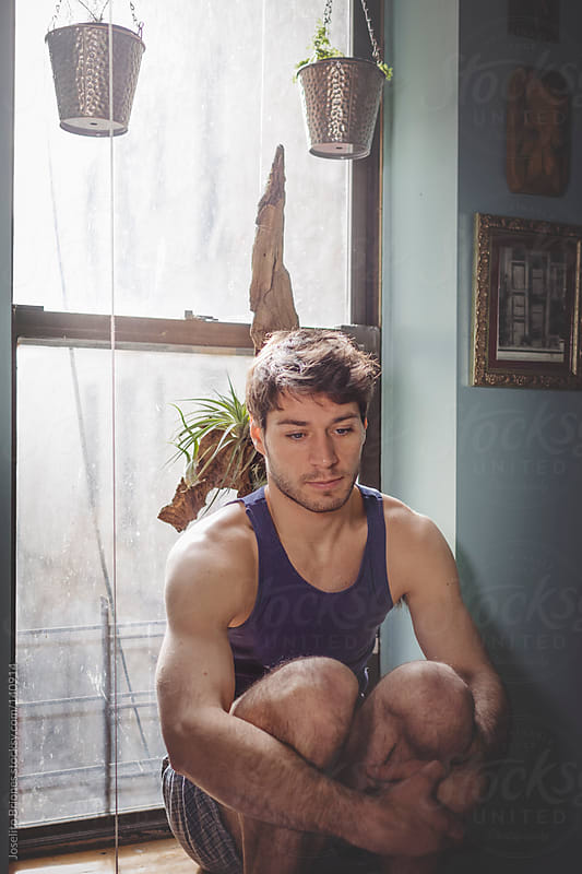 Relaxing Man in Reflective Mood Sitting on Window Sill at Home by Joselito Briones for Stocksy United
