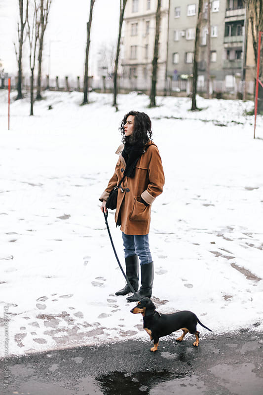 Curly woman with a dog, winter day  by Marija Kovac for Stocksy United