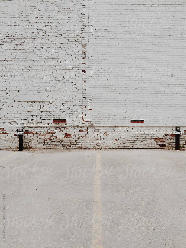 Old white brick building and parking lot by Carey Shaw for Stocksy United