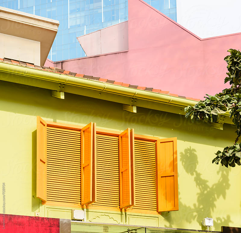 three orange windows with shutters on yellow wall by Lawren Lu for Stocksy United