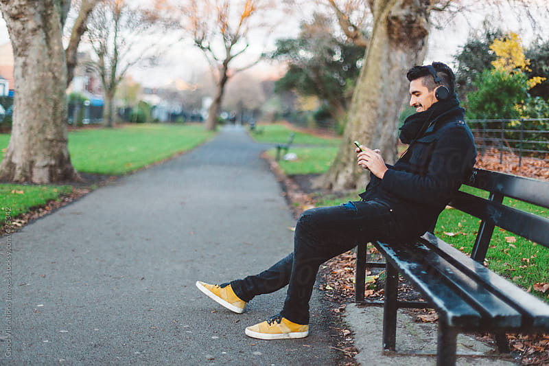 Man listening Music with Headphones sitting on a bench in a Park by Good Vibrations Images for Stocksy United