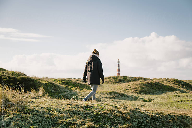Young female walking alone to the lighthouse in the background. by Koen Meershoek for Stocksy United