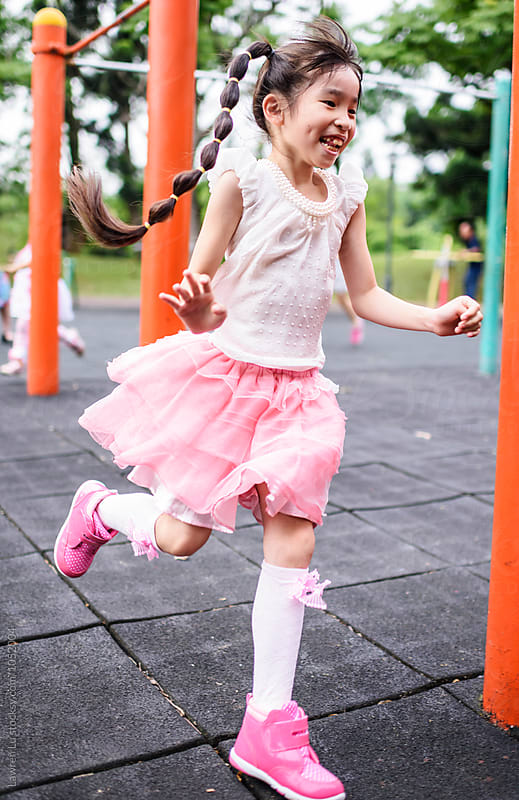 Cheerful little girl running on playground by Lawren Lu for Stocksy United